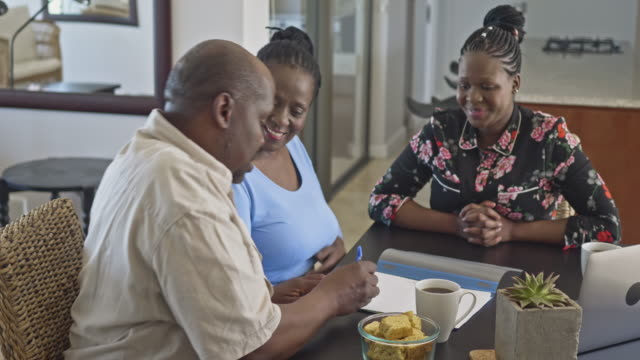 african mature couple signing a retirement contract with financial advisor at home - insurance agent stock videos & royalty-free footage