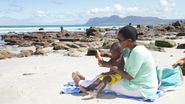 african mother and son at the beach, putting sunblock on - sun cream stock videos & royalty-free footage