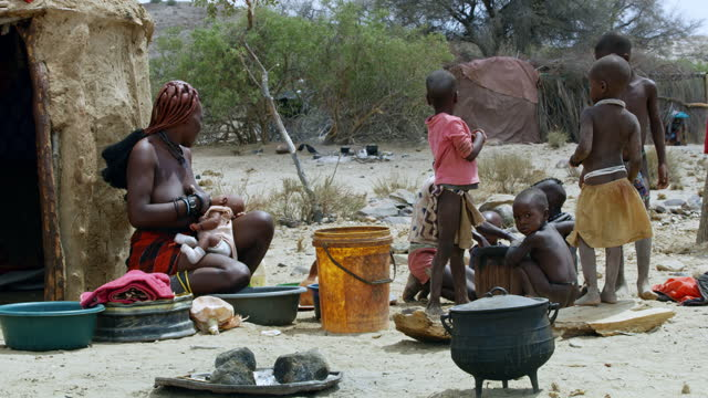african mother breast feeding baby outside hut with family, namibia, africa. real time. shot in 8k resolution. - 30 seconds or greater stock videos & royalty-free footage