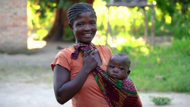 赤ちゃん息子と一緒に自宅でアフリカの母 - village点の映像素材/bロール