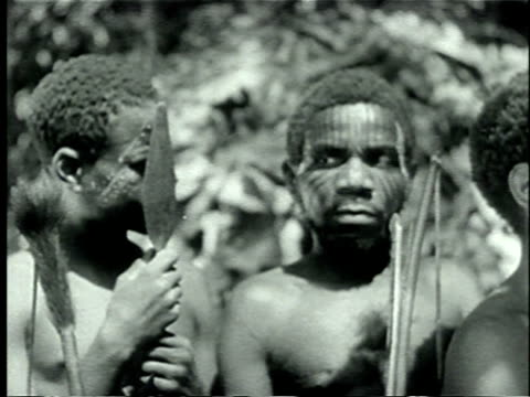 stockvideo's en b-roll-footage met 1939 montage african pygmy men wearing face paint and holding spears at traditional ceremony/ africa  - zij aan zij