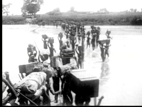 african safari porters cross river carrying supplies on head - the machine: master or slave stock videos & royalty-free footage
