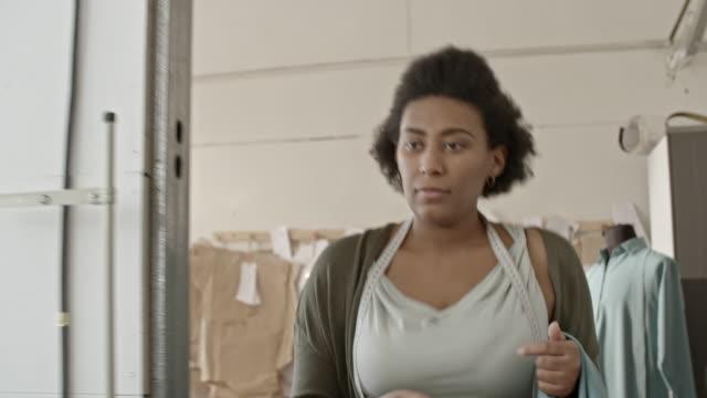 african seamstress with blue fabric choosing spool of thread - パタンナー点の映像素材/bロール