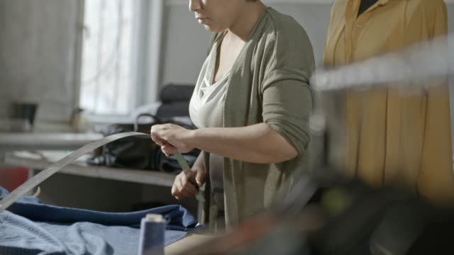 African seamstress working with fabric in workshop
