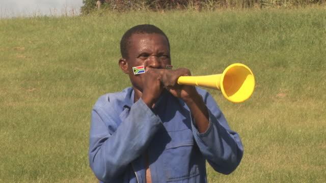 african soccer fan blowing horn vuvuzela - hd & pal - fan enthusiast stock videos and b-roll footage