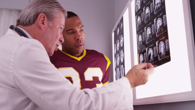 vídeos de stock, filmes e b-roll de african sports athlete looking at x-rays with caucasian doctor - physical injury