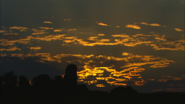 ws african sunset with clouds and rocky outcrop in foreground - outcrop stock videos & royalty-free footage