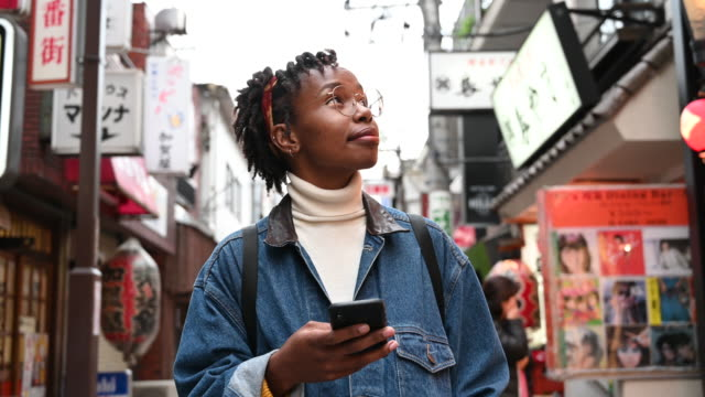 african tourist in japan using app on phone and looking around - direction stock videos & royalty-free footage