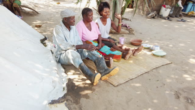 african village family having a casual banter while seated together - serene people stock videos & royalty-free footage
