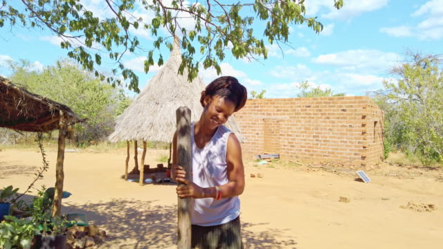 african village girl using mortar pestle to prepare corn maize - charity benefit stock videos & royalty-free footage