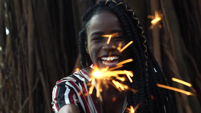 african woman burning sparklers - sparkler stock videos & royalty-free footage