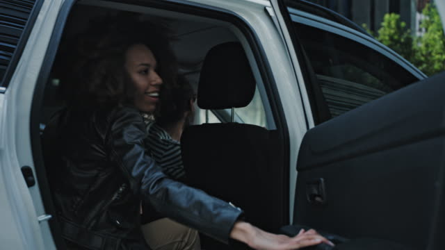 african woman catching an uber in the city center. getting into car - entering stock videos & royalty-free footage