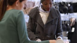 African woman chats with shop worker in clothing store
