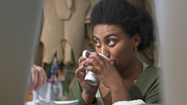 African woman chatting and enjoying sweet donut with tea