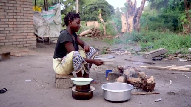 vídeos y material grabado en eventos de stock de la mujer africana que cocina alimentos en la aldea rural, malawi, áfrica - hambriento