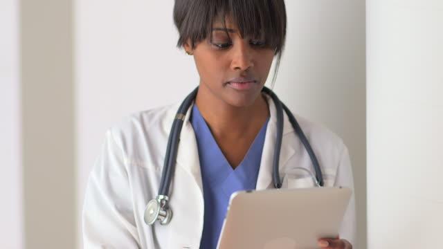 vidéos et rushes de african woman doctor working on tablet  - masque de chirurgien
