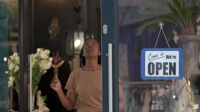 african woman hangs open sign and opens glass door of boutique store - store sign stock videos & royalty-free footage
