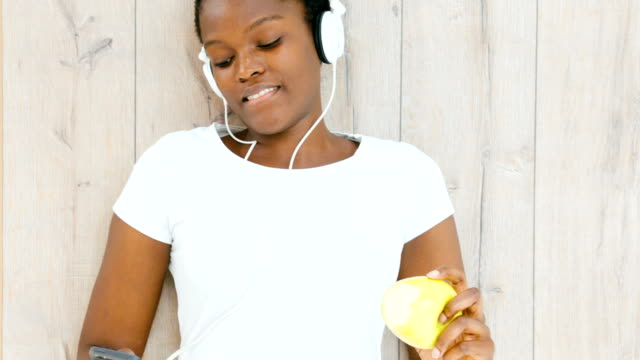 hd: african woman listening music and eating apple. - lying on back stock videos & royalty-free footage