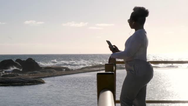 vídeos de stock, filmes e b-roll de mulher africana, ouvindo um podcast - na moda descrição