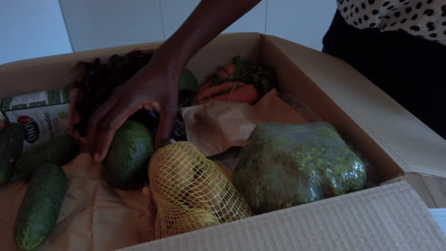 african woman taking out groceries out of box - organic stock videos & royalty-free footage
