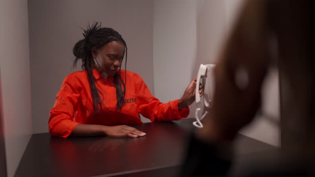 african woman talking with her girlfriend and crying during prison visit - prison jumpsuit stock videos & royalty-free footage