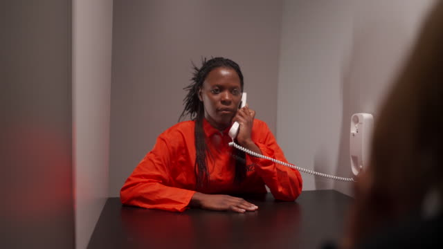 african woman talking with her girlfriend in visit room at prison - prison jumpsuit stock videos & royalty-free footage