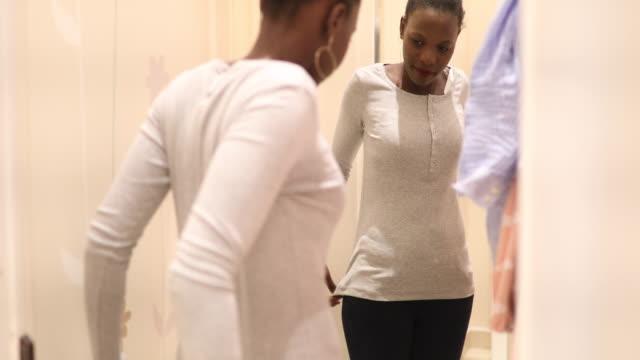 stockvideo's en b-roll-footage met afrikaanse vrouw proberen op kleding en zichzelf in de spiegel kijken - paskamer
