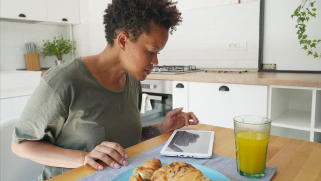 African woman using tablet while having breakfast.