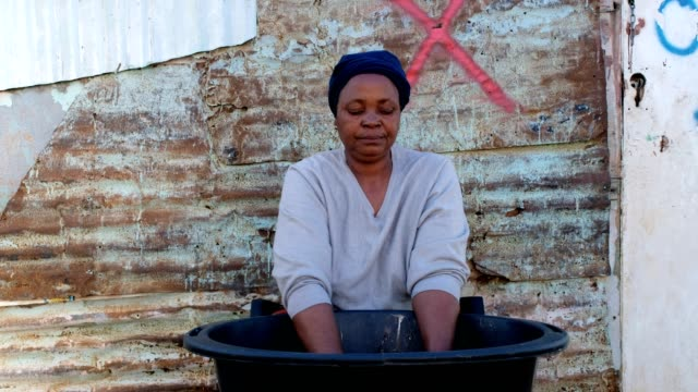 african woman washing her clothes - township stock videos & royalty-free footage