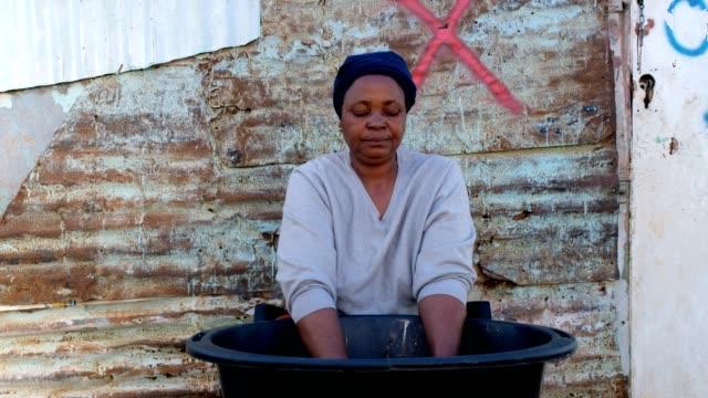 vidéos et rushes de femme africaine se lavant ses vêtements - cahute