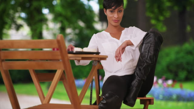 african woman with attitude poses flirtatiously while sitting outside - stiefel stock-videos und b-roll-filmmaterial
