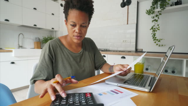 african woman working at home. - financial bill stock videos & royalty-free footage