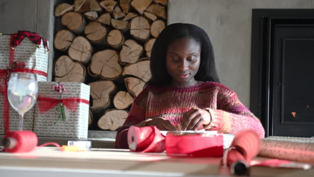 african woman wrapping gifts - wrapped stock videos & royalty-free footage