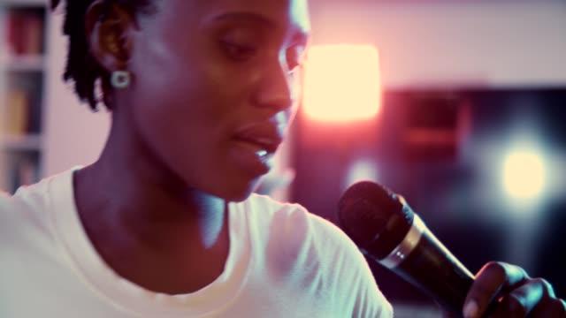 自宅でカラオケを歌うアフリカの女性 - 歌う点の映像素材/bロール