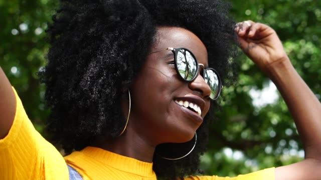 vídeos de stock, filmes e b-roll de jovem africana olhando para o outro lado no parque - olhar para o outro lado