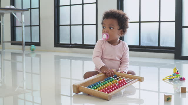 africana baby girl sitting still because don't know how to play wooden toy with innocence in the living room, concept of preschool, childhood, playing of a sibling. - 2 3 years stock videos & royalty-free footage