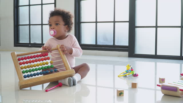 africana baby girl sitting to learn how to play wooden toy with innocence in the living room, concept of preschool, childhood, playing of a sibling. - 2 3 years stock videos & royalty-free footage