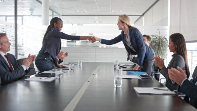 african-american and caucasian businesswoman shaking hands after signing a contract in front of their project teams in the conference room - businesswoman stock videos & royalty-free footage