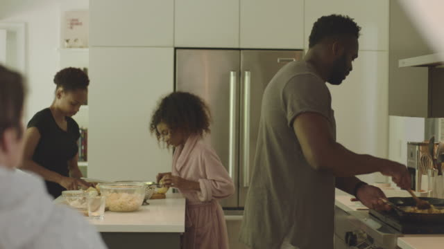 african-american and mixed race family making breakfast together in their kitchen - chores stock videos & royalty-free footage