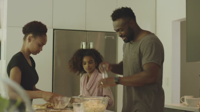African-American and mixed race family making breakfast together in their kitchen