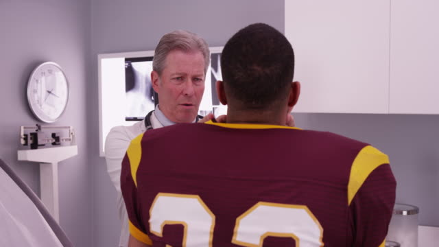 vídeos de stock, filmes e b-roll de african-american athlete having neck injury examined by doctor - physical injury