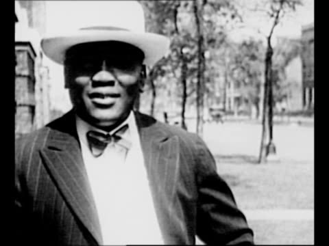 africanamerican boxer jack johnson shadowboxes in ring / cu johnson smiles as he sits in car / montage johnson in suit speaking smiling and showing... - 1910 stock-videos und b-roll-filmmaterial