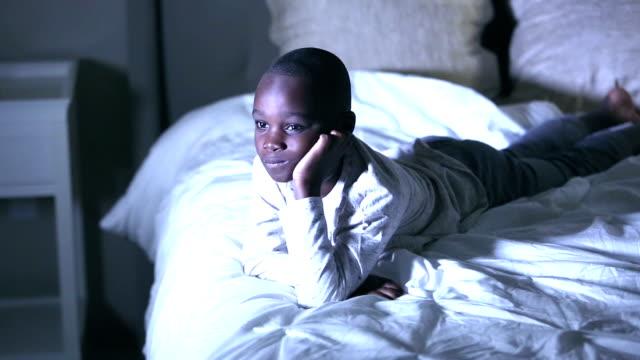 vidéos et rushes de garçon afro-américain dans la chambre à coucher regardant la tv - enfant d'âge scolaire