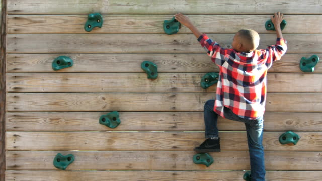 african-american boy on climbing wall - parco giochi video stock e b–roll