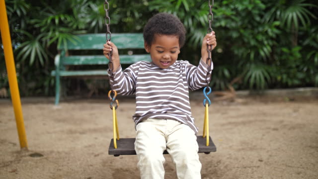 african-american boy playing on playground swing - swing stock videos & royalty-free footage