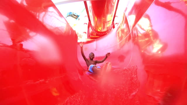 african-american boy sliding down water slide - water slide stock videos & royalty-free footage