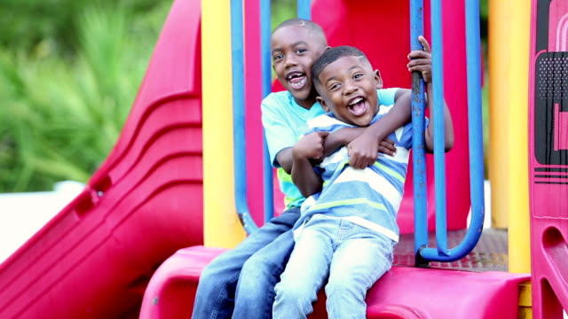 African-American brothers climbing on playground slide