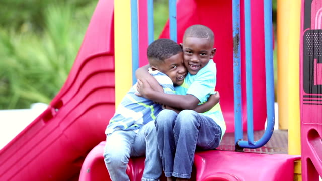 African-American brothers sitting on slide, hugging