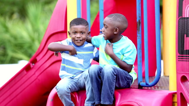 african-american brothers sitting on slide - african american ethnicity stock videos & royalty-free footage