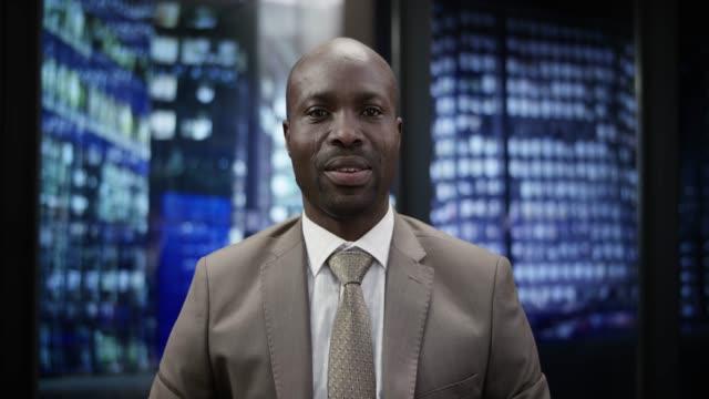 afro-amerikansk affärsman på ett videosamtal från kontoret på natten - förgrundsfokus bildbanksvideor och videomaterial från bakom kulisserna